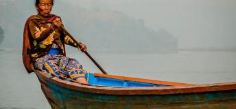 Woman rowing boat in Nepal.