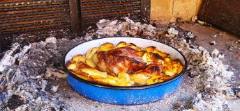 Chicken and potatoes cooked on an outside grill.