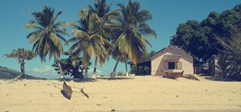 A small house by the sea surrounded by palm trees in the island of Madagascar