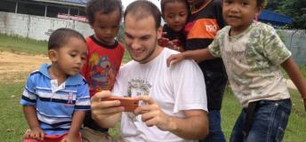 Children surrounding man looking at phone