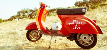 "Red vespa with ""all you need is love"" written on it"