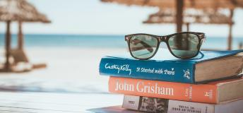 Stack of books and glasses at beach.