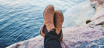 Girl wearing ankle boots propping her feet up near a coast