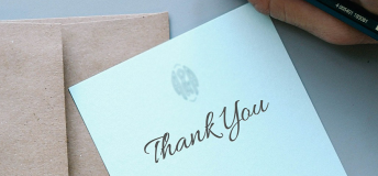 Thank you card with envelope and hand holding a pencil