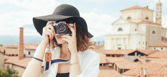 woman in black hat snapping a photo with a film camera