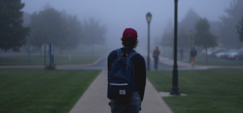 Boy walking on a college campus