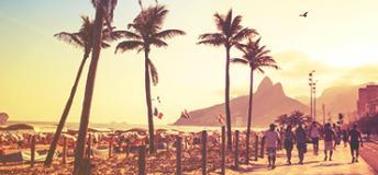 People walking by the side of a beach in Brazil.