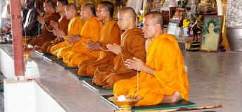 Thai monks praying in a temple