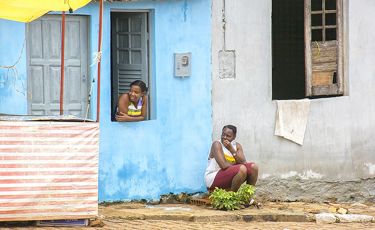 Two women outside houses in Salvador, Brazil