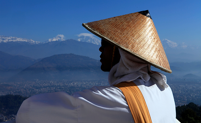 Monk overlooking a mountain with a straw hat on
