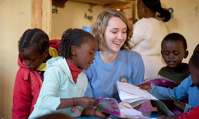 Volunteer reading to children in Africa