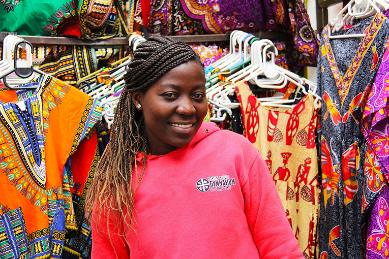 African teen smiling at a clothing market